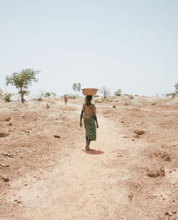 A woman carries excavated soil from a mine shaft on her head. At the artisanal gold mines of Bouda, Burkina Faso, March 2014