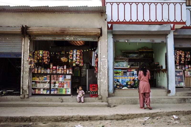 Ein Kind isst auf der Treppe vor einem Laden in den Straßen Kathmandus, Nepal, 2015.