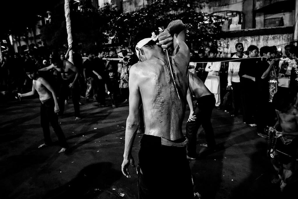 Ein junge zerschneidet seinen Rücken mit einem kurzen Schwert während des Ashura-Trauerfests in Mumbai, Indien, 2015.