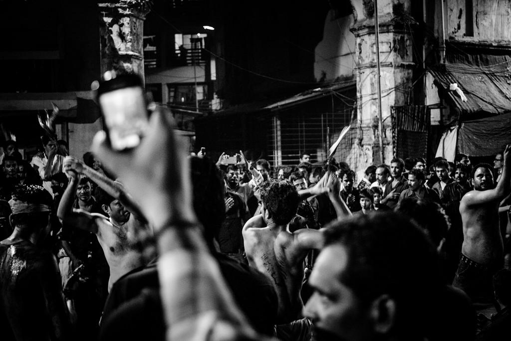 Ein Mann filmt Gläubige Schiiten bei der Selbstkasteiung während des Ashura-Trauerfests in Mumbai, Indien, 2015.
