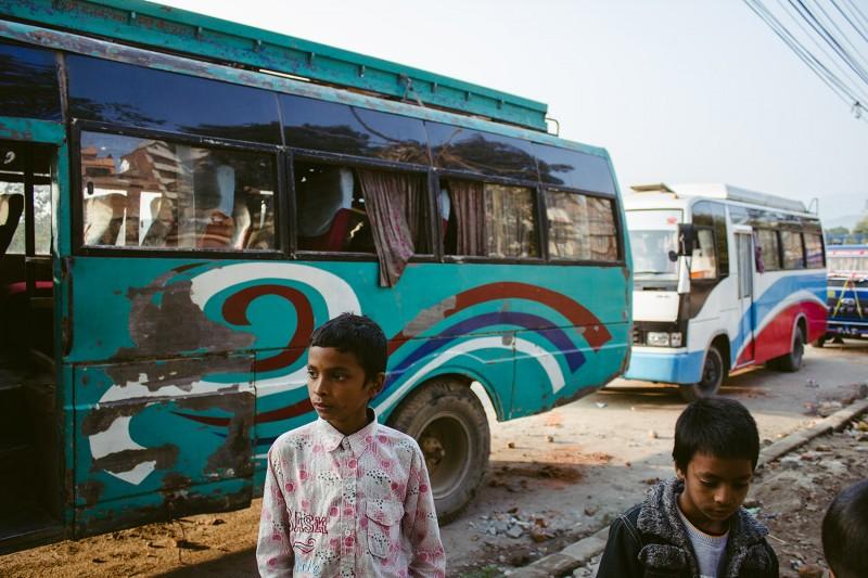 Eine Gruppe von Kindern steht vor einer Schlange alter Busse in Kathmandu.