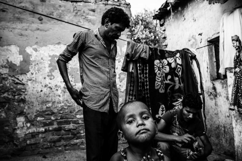 Puppenspieler Jagdish, sein Sohn und sein Enkelkind im Kathputli Slum, Neu-Delhi.