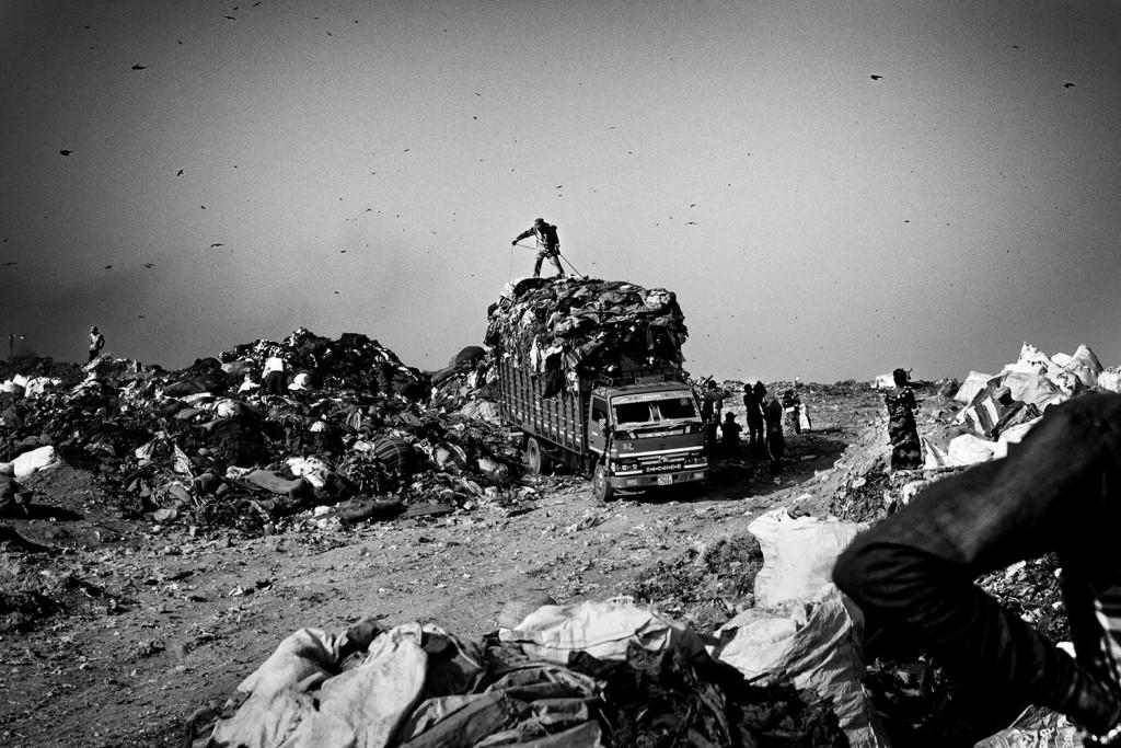 Ein Mann steht auf einem mit Müll beladenen LKW in Ghazipur, Neu-Delhi, 2015.