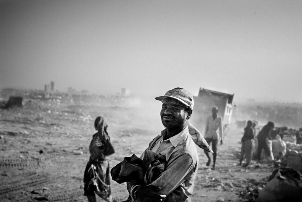 Ein Mann trotzt dem Staub auf der Ghazipur Müllkippe und blickt zur Kamera, Neu-Delhi, 2015.
