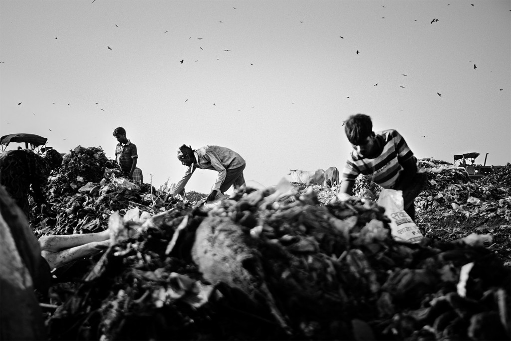 Frauen und Männer sammeln verwertbare Materialien in Säcken auf dem Ghazipur Müllberg, Neu-Delhi, 2015.