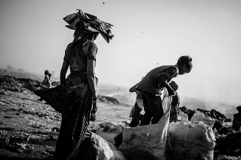 Frauen und Männer sammeln verwertbare Materialien in Säcken auf der Ghazipur Müllkippe, Neu-Delhi, 2015.