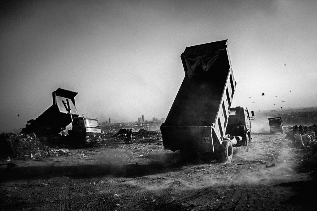 LKW laden ihren Müll auf dem Ghazipur Müllberg ab, Neu-Delhi, 2015.