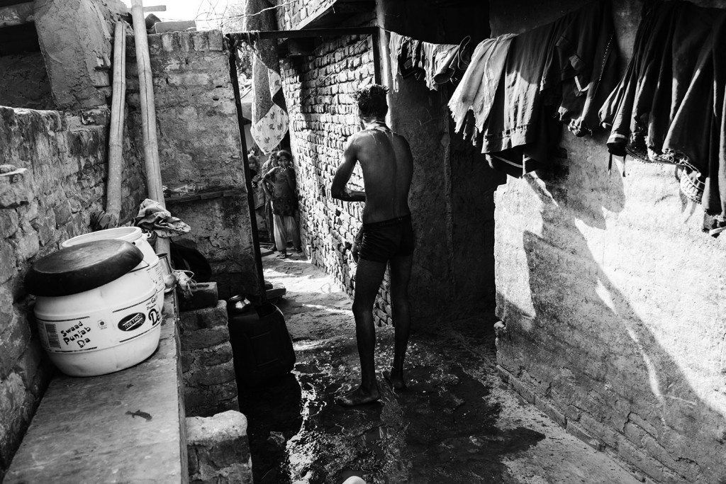 Jagdishs ältester Sohn nimmt ein Bad im Kathputli-Slum, Neu-Delhi, 2015.