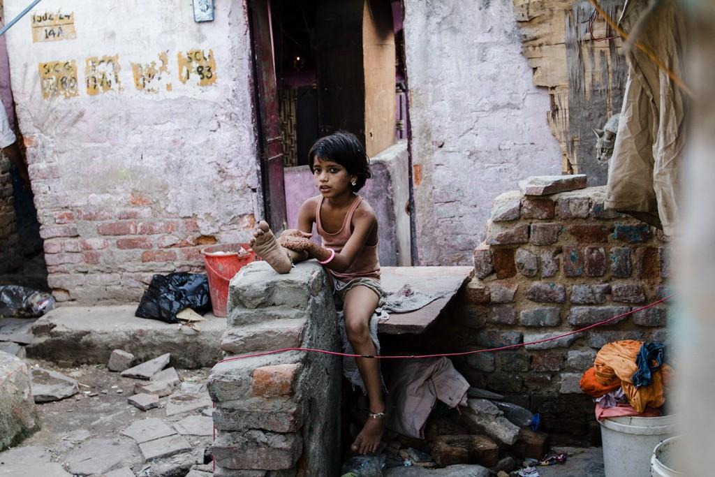Ein Kind sitzt auf einer Steinmauer in der Kathputli Colony, Neu-Delhi, 2015.