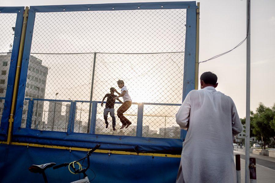 Ein Wanderarbeiter schaut seinen Kindern dabei zu, wie sie sich auf einer Kirmes am Straßenrand amüsieren. Dubai, VAE 2016