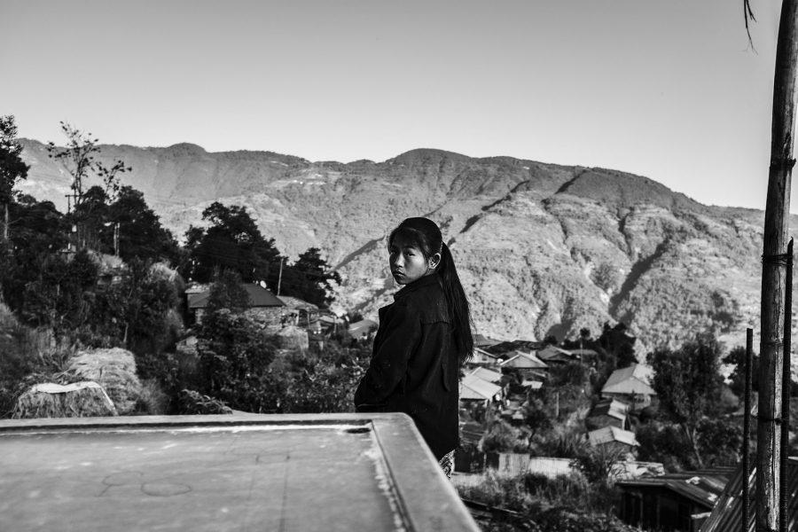 Ein Mädchen steht auf der Terasse eines unfertigen Hauses in einem Dorf im Distrikt Sindhupalchok. Nepal, 2016