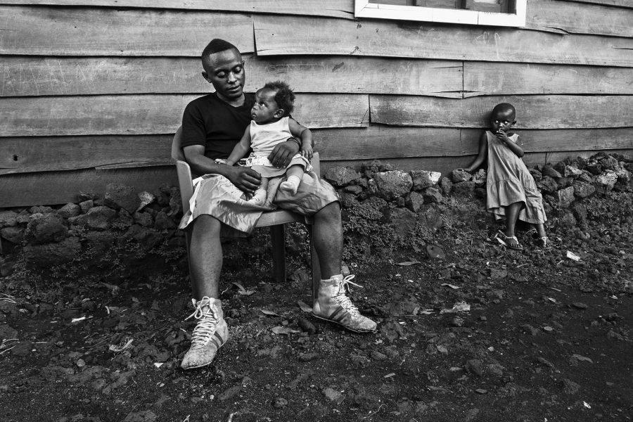 Ein junger Boxer und seine Familienmitglieder vor dem Haus der Eltern, DR Kongo 2016.