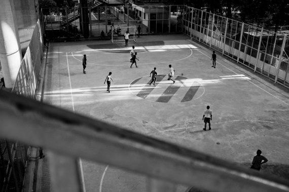 Hobby-Sportler spielen Fußball auf einem öffentlichen Fußballplatz unter einer Brücke in Bangkok, Thailand, 2017.