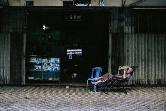 Eine alte Frau liegt in einem Liegestuhl vor ihrem Familiengeschäft in Phnom Penh, Kambodscha, 2017.